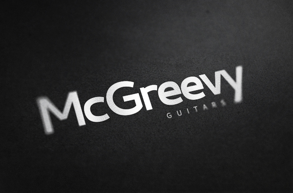 Brand name against dark textured paper - McGreevy Guitars